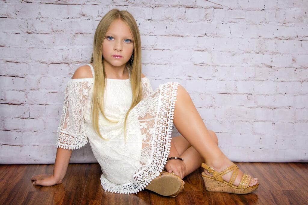 blonde girl in lace dress sitting modeling